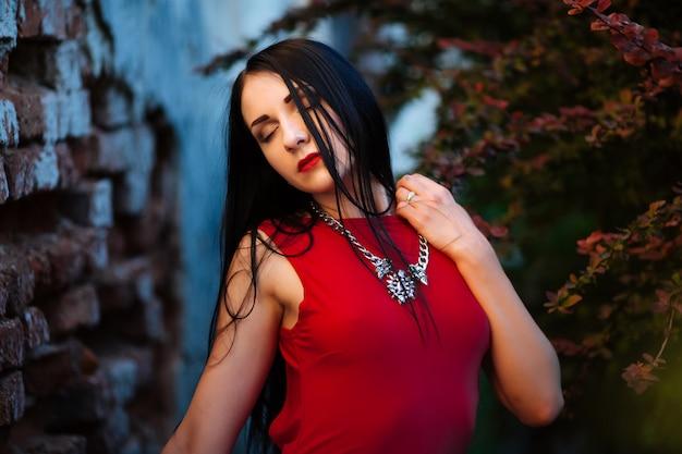 Ritratto di bellezza di moda. bella donna con i capelli ricci che indossa un abito rosso di moda, in piedi contro il muro, chiuse gli occhi