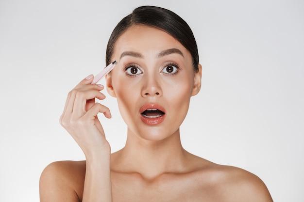 Ritratto di bellezza di sensuale donna bruna con i capelli nel panino che esprime dolore in faccia mentre pizzicando le sopracciglia con le pinzette, isolato sopra bianco
