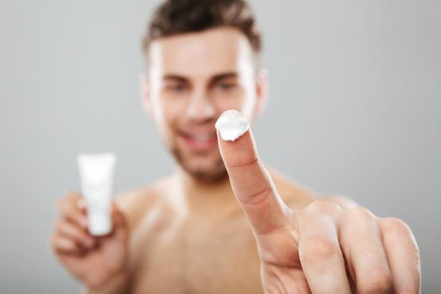 Ritratto di bellezza di un uomo mezzo nudo applicando la crema per il viso