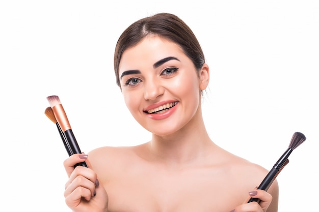 Ritratto di bellezza di una bella donna mezza nuda felice che tiene insieme di pennelli trucco