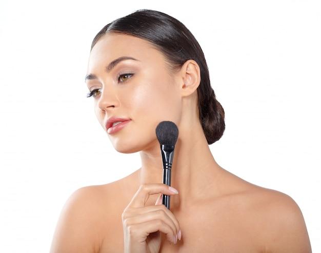 Ritratto di bellezza di una bella donna mezza nuda giocosa applicare il make-up con un pennello
