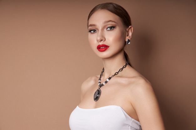 Ritratto di bellezza di una donna con gioielli, orecchini nelle orecchie e una collana al collo.