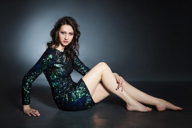 Ritratto di bellezza di una donna con il trucco sera bella seduta sul pavimento, donna bruna in un abito da sera lucido con paillettes. cosmetici naturali per il viso