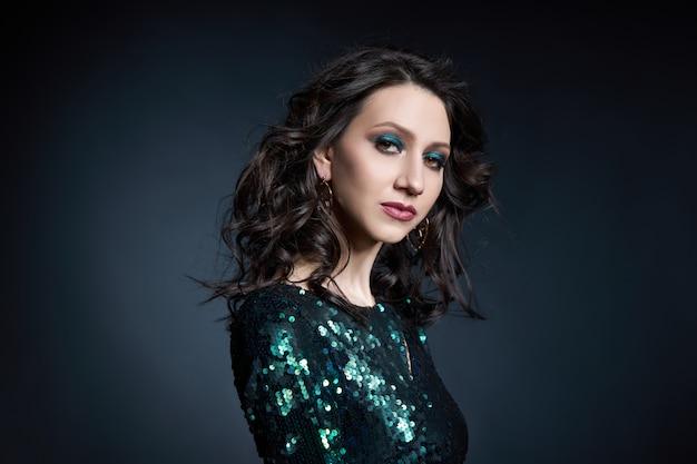 Ritratto di bellezza di una donna con un bel trucco da sera, donna bruna in un abito da sera lucido con paillettes. cosmetici naturali per il viso
