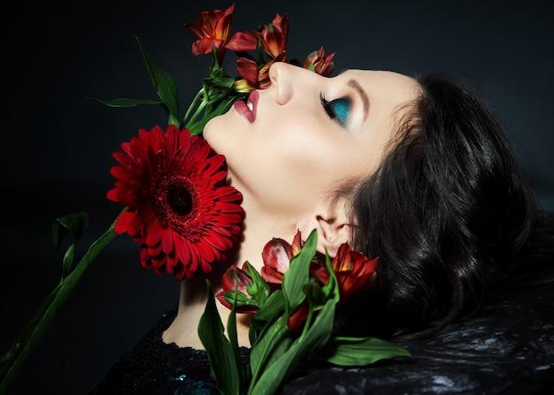 Ritratto di bellezza di una donna con un bel trucco da sera e fiori sul viso, una donna bruna in un abito da sera lucido con paillettes. cosmetici naturali per il viso, petali di fiori