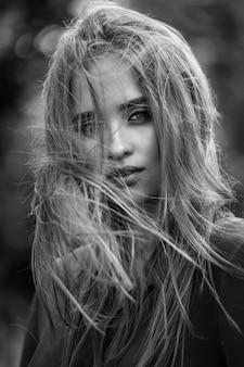 Ritratto di bellezza di una giovane bella ragazza bruna con lunghi capelli neri dritti volanti. capelli magnifici. bianco e nero