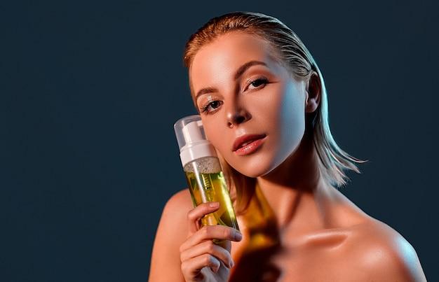 Ritratto di bellezza di una giovane donna attraente che controlla parete nera con schiuma detergente facciale.