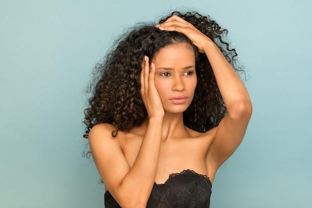 Ritratto di bellezza di una giovane ragazza nera seria sul blu