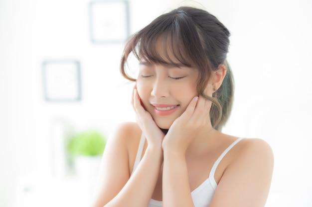 Ritratto di bello giovane sorriso asiatico della donna mentre sveglia sano