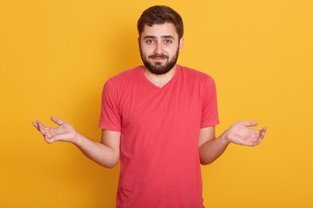 Ritratto di bello giovane uomo barbuto caucasico con capelli scuri, maschio bello che guarda direttamente la macchina fotografica con emozione confusa