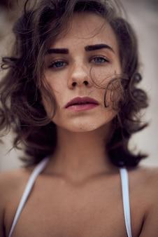 Ritratto di bello modello caucasico della donna preso il sole con capelli lunghi scuri in costume da bagno a strisce che si trova sulla spiaggia di estate con la sabbia bianca. vista dall'alto