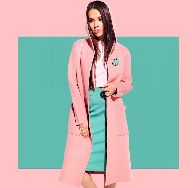 Ritratto di bello modello caucasico sorridente della donna castana in soprabito luminoso e gonna alla moda di estate che posano sul fondo rosa e blu