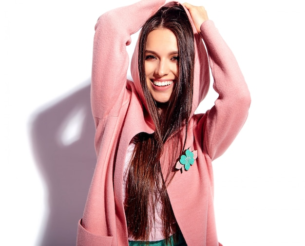 Ritratto di bello modello caucasico sorridente della donna castana in soprabito rosa luminoso
