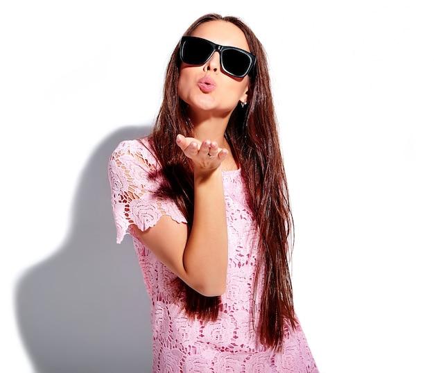 Ritratto di bello modello caucasico sorridente della donna castana in vestito alla moda da estate rosa luminosa in occhiali da sole isolati su fondo bianco. dare un bacio