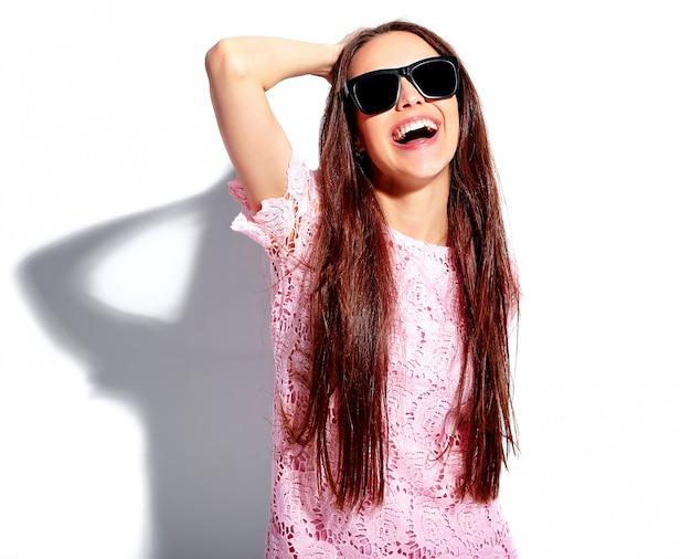 Ritratto di bello modello caucasico sorridente della donna castana in vestito alla moda da estate rosa luminosa in occhiali da sole isolati su fondo bianco