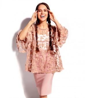 Ritratto di bello modello caucasico sorridente della donna del brunette con le doppie trecce in vestiti alla moda di estate rosa luminosa isolati su priorità bassa bianca.
