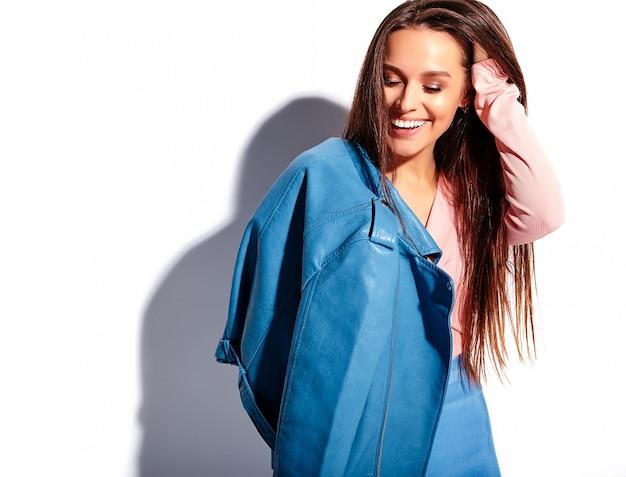 Ritratto di bello modello caucasico sorridente della donna del brunette in vestiti alla moda di estate dentellare e blu luminosi isolati su priorità bassa bianca