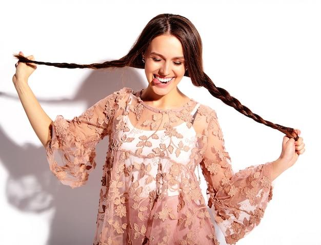 Ritratto di bello modello caucasico sorridente della donna del brunette in vestiti alla moda di estate dentellare luminosa isolati su priorità bassa bianca.