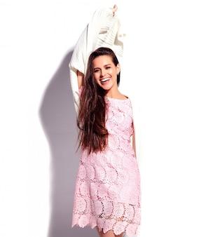 Ritratto di bello modello caucasico sorridente della donna del brunette in vestito alla moda da estate dentellare luminosa isolato su priorità bassa bianca. celebrando