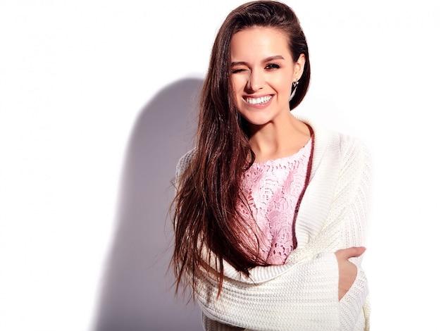 Ritratto di bello modello caucasico sorridente della donna del brunette in vestito alla moda da estate dentellare luminosa isolato su priorità bassa bianca. mordendosi il labbro