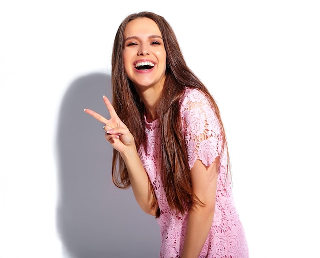 Ritratto di bello modello caucasico sorridente della donna del brunette in vestito alla moda da estate dentellare luminosa isolato su priorità bassa bianca. mostra del segno di pace
