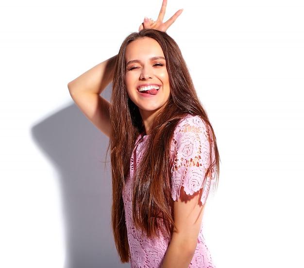 Ritratto di bello modello caucasico sorridente della donna del brunette in vestito alla moda da estate dentellare luminosa isolato su priorità bassa bianca. mostrando la sua lingua e il segno di pace
