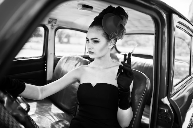 Ritratto di bello modello sexy della ragazza di modo con trucco luminoso nel retro stile che si siede in automobile d'annata con una sigaretta a disposizione.