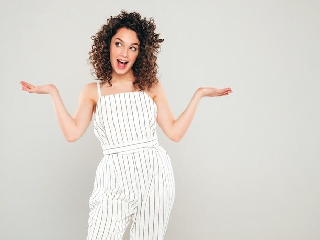 Ritratto di bello modello sorridente con l'acconciatura dei riccioli afro vestita in vestiti hipster estate ragazza sexy spensierata che mostra qualcosa su entrambe le mani piatte per una scelta simile del prodotto