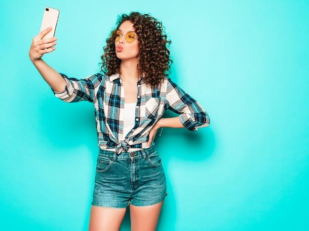 Ritratto di bello modello sorridente con l'acconciatura dei riccioli di afro vestita in vestiti dei pantaloni a vita bassa di estate ragazza spensierata sexy che posa nello studio su fondo grigio la donna divertente alla moda prende la foto del selfie