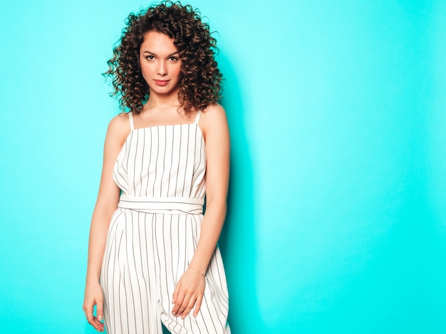 Ritratto di bello modello sorridente con l'acconciatura dei riccioli di afro vestita in vestiti dei pantaloni a vita bassa di estate ragazza spensierata sexy che posa vicino alla parete blu donna divertente e positiva alla moda
