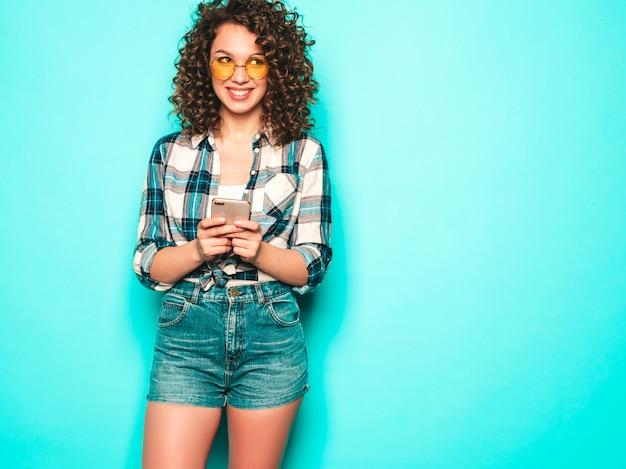 Ritratto di bello modello sorridente con l'acconciatura dei riccioli di afro vestita in vestiti di estate ragazza libera che posa vicino alla parete blu la donna usa il suo telefono cellulare e la battitura a macchina degli sms. sta cercando le vendite del negozio