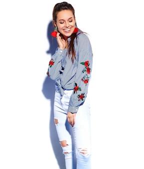 Ritratto di bello modello sorridente della donna del brunette dei pantaloni a vita bassa in vestiti blu alla moda casuali isolati su bianco