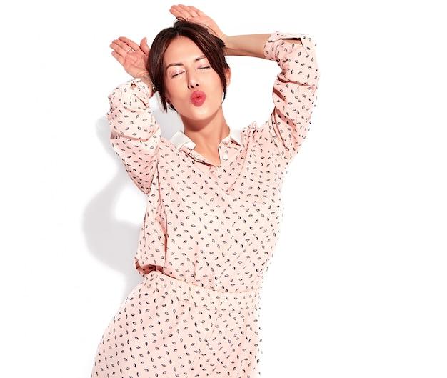 Ritratto di bello modello sveglio della donna del brunette in vestiti casuali di estate senza trucco isolato su bianco. fare orecchie da coniglio e dare un bacio d'aria