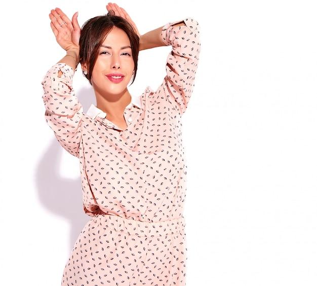 Ritratto di bello modello sveglio della donna del brunette in vestiti casuali di estate senza trucco isolato su bianco. fare orecchie di coniglio
