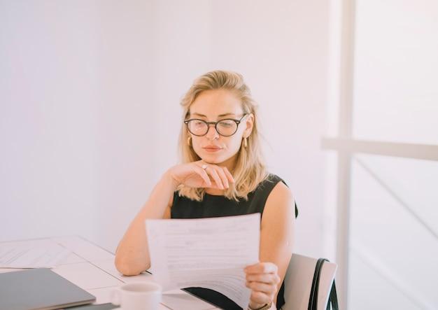 Ritratto di bionda giovane imprenditrice leggendo il documento