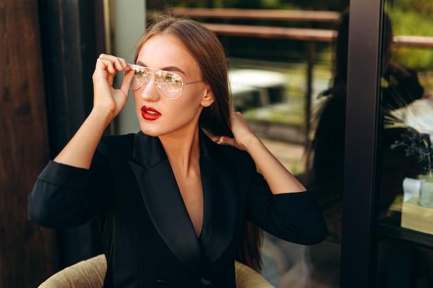 Ritratto di bionda imprenditrice tocca i suoi occhiali e guardando lateralmente.- immagine orizzontale