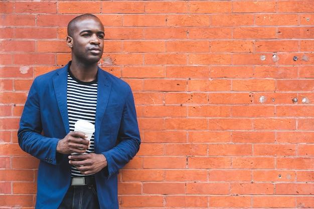 Ritratto di black guy holding coffee. copyspace