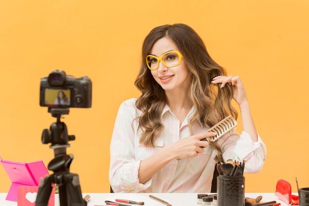 Ritratto di blogger che spazzola i capelli sulla macchina fotografica