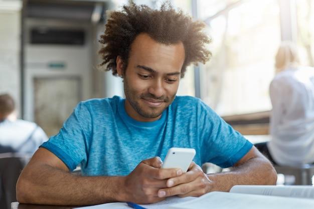 Ritratto di blogger maschio nero con capelli ricci che indossa maglietta casual blu che tiene smart phone moderno utilizzando connessione internet ad alta velocità, messaggi di testo ai suoi amici seduti al bar