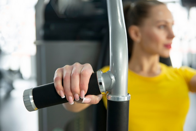 Ritratto di blured di giovane donna caucasica che risolve sulla macchina di esercizio all'interno della palestra