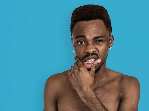 Ritratto di bocca toccante petto nudo di uomo africano