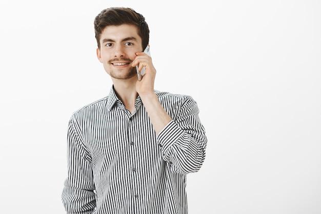 Ritratto di boufriend caucasico spensierato ordinario con barba e baffi, parlando sullo smartphone e sorridendo gioiosamente, sentendosi fiducioso e soddisfatto mentre chiede alla ragazza all'appuntamento sul muro grigio
