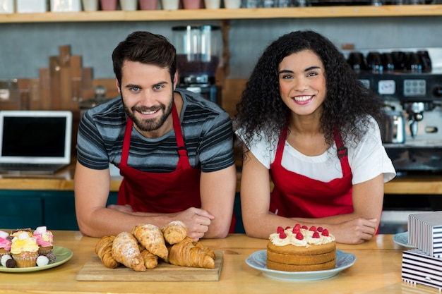 Ritratto di cameriere e cameriera appoggiato sul bancone