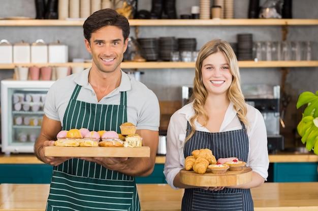 Ritratto di cameriere e cameriera in possesso di un vassoio di cupcakes