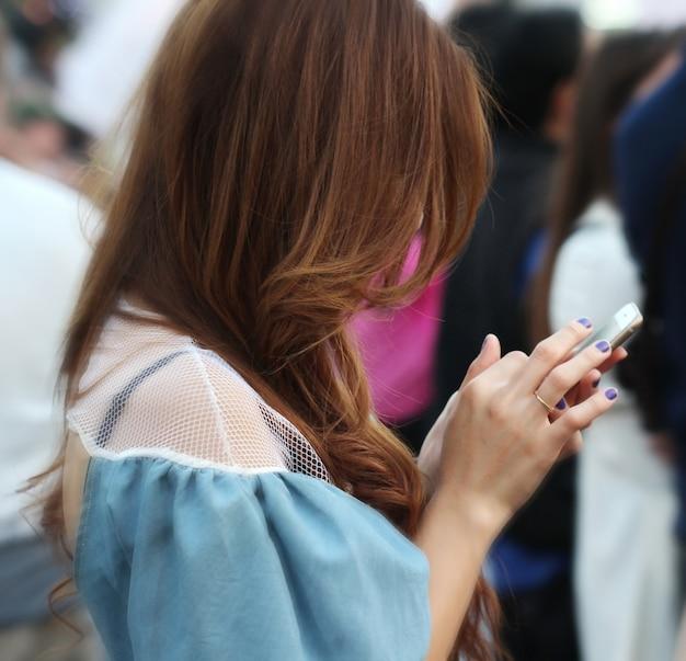 Ritratto di capelli lunghi donna con la barba vestita in abiti eleganti in chat sul telefono cellulare