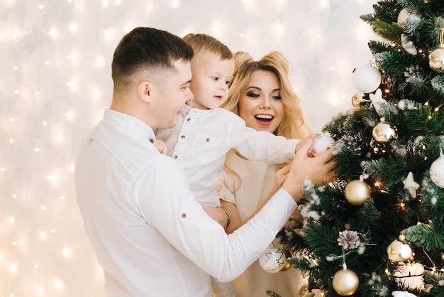 Ritratto di capodanno di una bellissima giovane famiglia. genitori attraenti e un figlio piccolo decorano un albero di natale