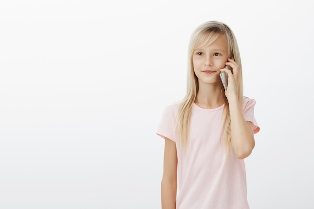 Ritratto di carina giovane figlia con capelli biondi, tenendo lo smartphone vicino all'orecchio e guardando da parte con espressione soddisfatta concentrata, parlando con il fratello