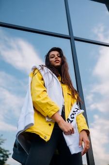 Ritratto di carino bella giovane donna divertendosi e in posa all'aperto. attraente ragazza alla moda allegro alla moda hipster che cammina per le strade della città.