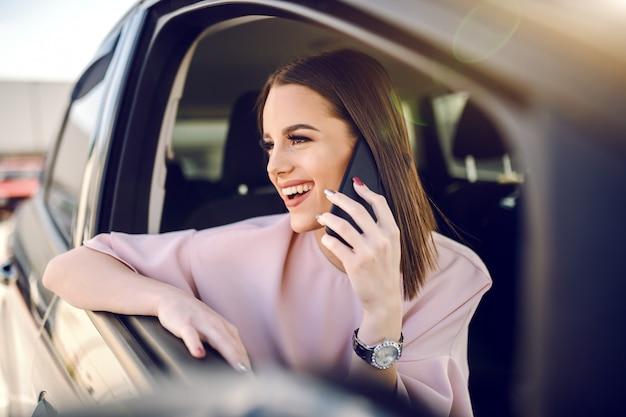 Ritratto di castana elegantemente vestito splendido che per mezzo dello smart phone mentre appoggiandosi il finestrino della macchina.