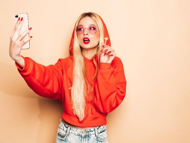 Ritratto di cattiva ragazza dei giovani bei pantaloni a vita bassa in vestiti d'avanguardia dei jeans e orecchino nel suo naso la donna bionda sorridente spensierata sexy prende il selfie modello positivo che lecca intorno allo zucchero candito